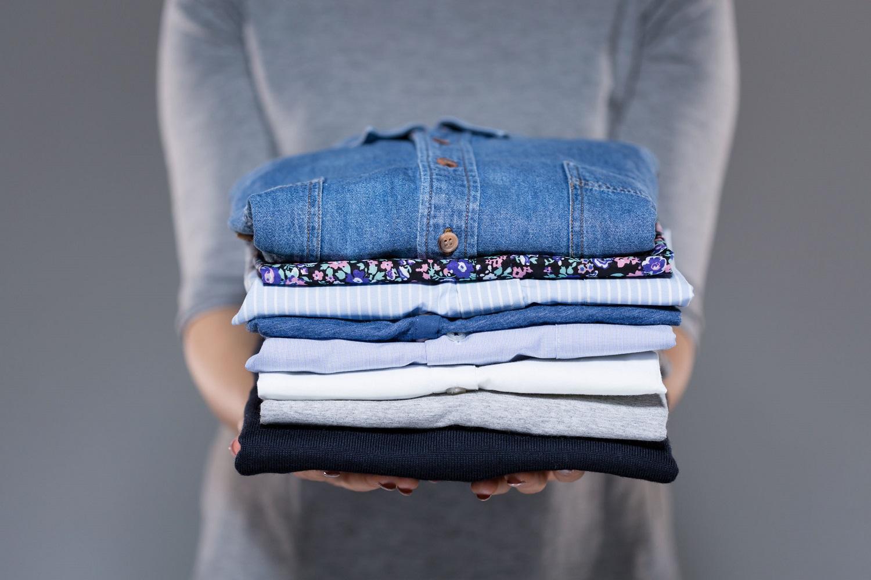 אישה מחזיקה בגדים מקופלים