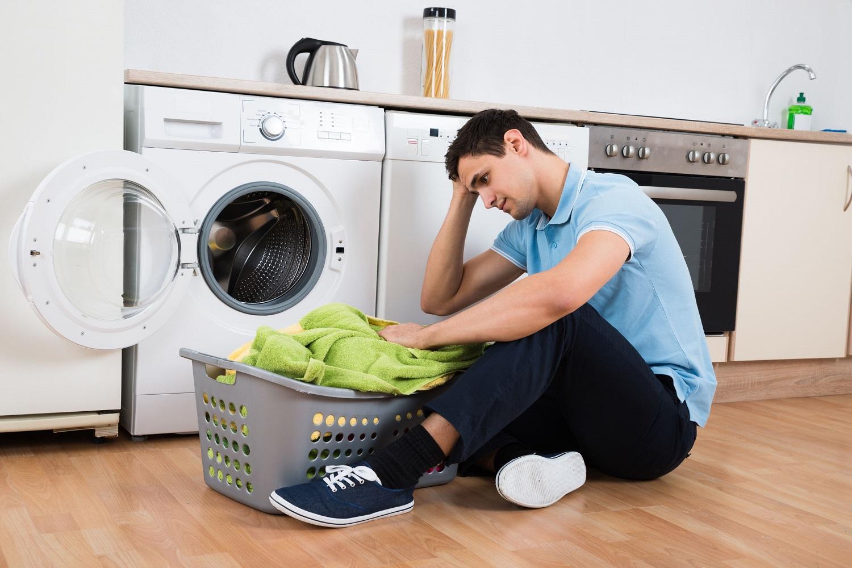 בחור מיואש יושב ליד מכונת כביסה עם סל כביסה