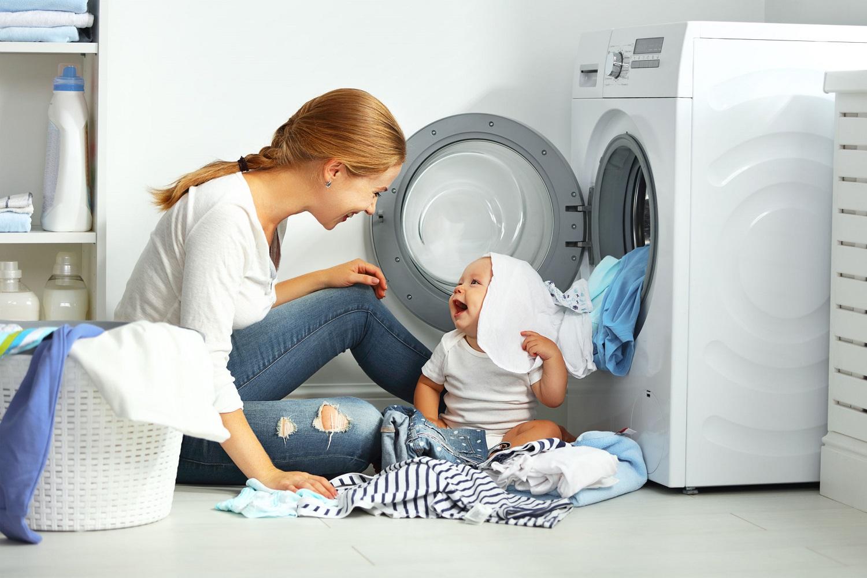 אמא יושבת עם תינוק על הרצפה מלאה בכביסה